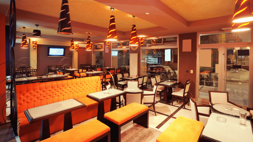 Inside a restaurant with stunning cone-shaped lights with white tables and yellow sofas and chairs. Great for picture of customers that they can post on their social media accounts.