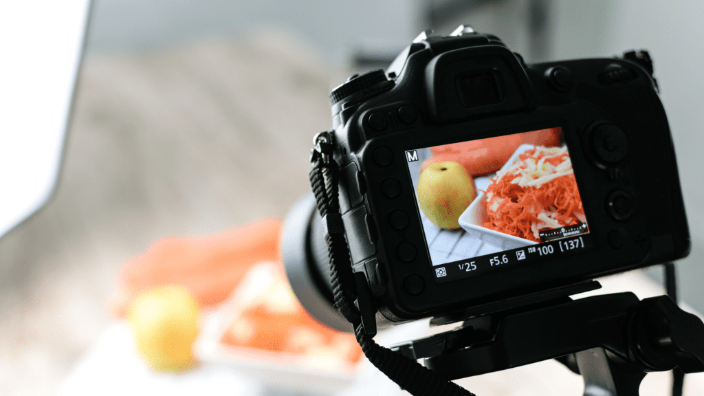 DSLR camera snapping a photo of a salad and an apple. This way restaurant and takeaways get to update customers to help their social media marketing.